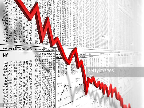 Down graph in front of newspaper stock market tables