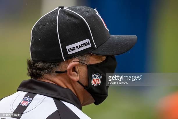"""Down Judge Jim Mello looks on while wearing a heat with an """"End racism"""" logo during the first half of the game between the Washington Football Team..."""