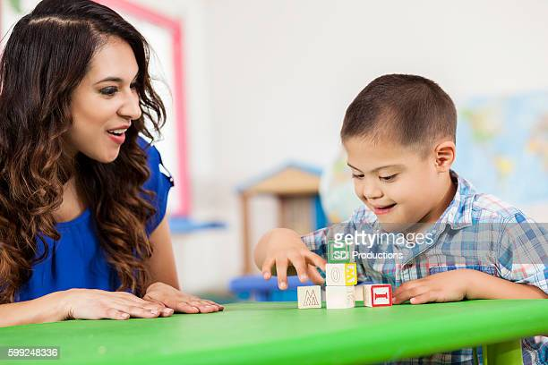 Down Syndrome boy playing with building blocks at daycare