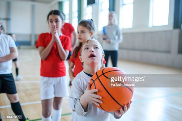 down syndrome boy with pupils exercising indoors in gym class, playing basketball. - disability stock pictures, royalty-free photos & images