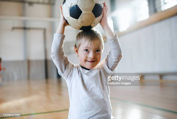 down syndrome child with soccer ball indoors in gym class, looking at camera. - disability stock pictures, royalty-free photos & images