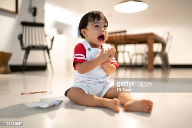 Down Syndrome Little Boy Playing at Home