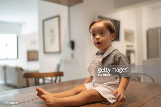 Down Syndrome Little Boy Sitting on Dinning Table