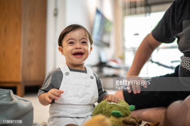down syndrome son playing at home - down syndrome stock pictures, royalty-free photos & images
