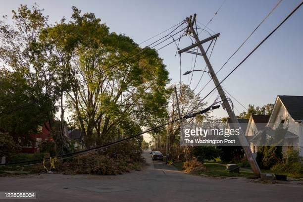 Downed power line leans over a street in Cedar Rapids, Iowa on Sunday, August 16, 2020. A rare Derecho storm battered large sections of Cedar Rapids...