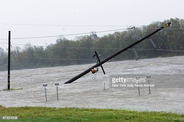 Downed utility pole and power lines list precariously over floodwaters in Port Arthur Tex and signs warning of underground propylene and ethylene...
