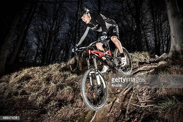Downhill enduro mountain bike jump in the woods.