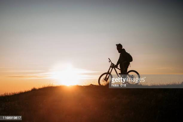 downhill mountain biking in dawn - downhill skiing stock pictures, royalty-free photos & images