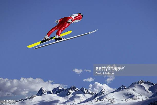Downhill skier jumping, rear view (digital composite)