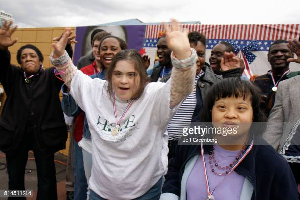 Down's Syndrome men and women showing off their medals at the Association for Development of Exceptional, MLK Day Carnival.