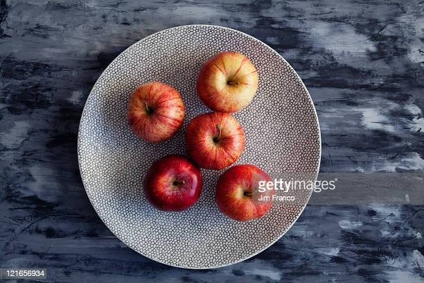 downshot of apples on textured plate and table