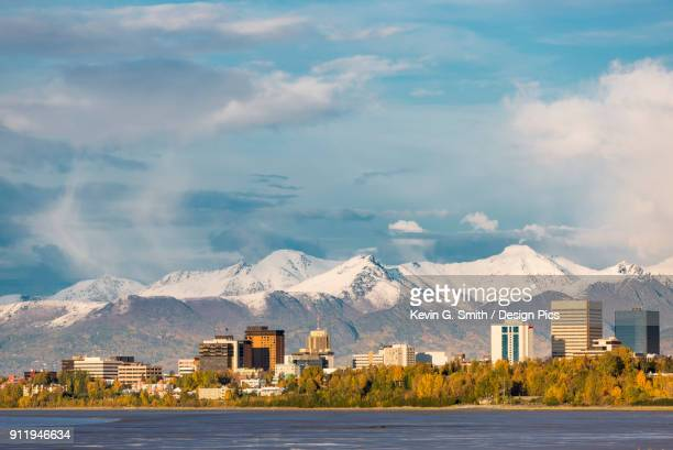 downtown anchorage as seen from point woronzof, atmospheric clouds shrouding the chugach mountains in the background, autumn coloured trees on the shoreline, south-central alaska - anchorage alaska stock photos and pictures