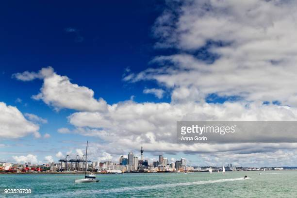 Downtown Auckland skyline seen across harbour from ferry to Rangitoto Island on partly cloudy summer afternoon, North Island New Zealand