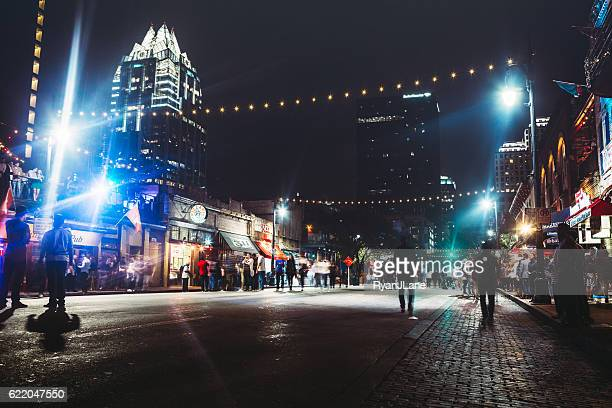 downtown austin at night on sixth ave - downtown district stock pictures, royalty-free photos & images