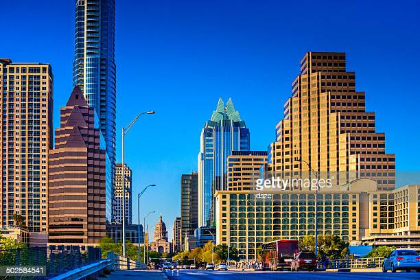 Downtown Austin skyscrapers surrounding Texas Capitol with busy cars, people