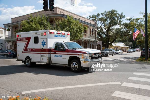 Downtown Fairhope Alabama USA An ambulance on an emergency call trailing through the town center