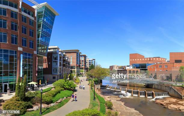 downtown greenville with development along reedy river - greenville south carolina stock pictures, royalty-free photos & images