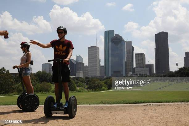 Downtown high-rises are pictured behind people on a Segway tour by Buffalo Bayou on August 25, 2018 in Houston, Texas. August 25 is the one-year...