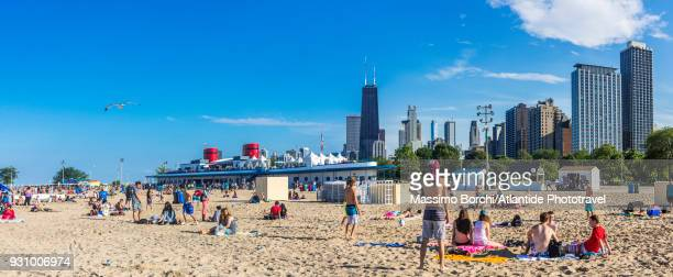 downtown, lincoln park, north avenue beach on lake michigan, the steam boat-shaped bar and the town with john hancock center skyscraper on the background - north avenue beach stock pictures, royalty-free photos & images