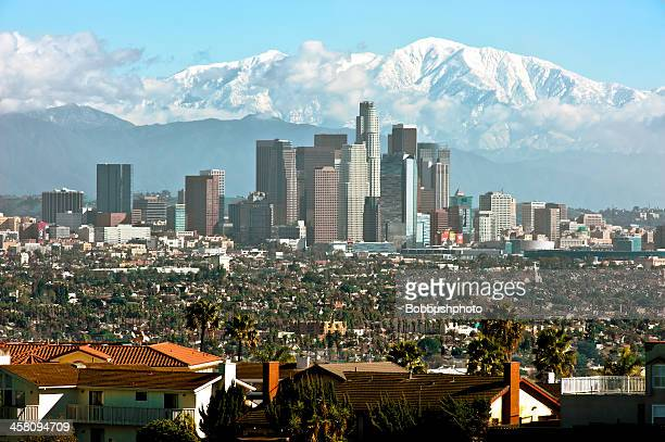downtown los angeles, snow covered san gabriels - mount baldy stock photos and pictures