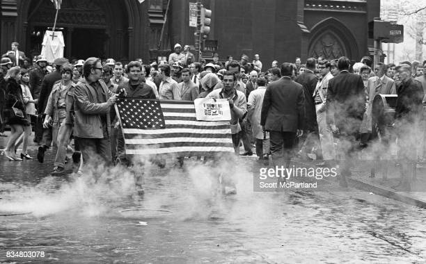 Downtown Manhattan May 1970: A group of construction workers hold an American Flag in front of them, and march near Wall Street, protesting Mayor...