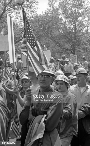 A middle aged man stands with an American Flag in hand along side construction workers and war veterans alike to protest Mayor Lindsey's decision to...