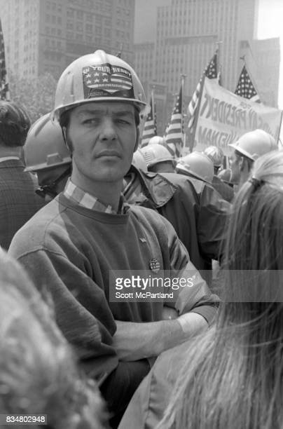 An angry man stands with arms crossed along side his fellow construction workers to protest Mayor Lindsey's decision to lower the American Flags...