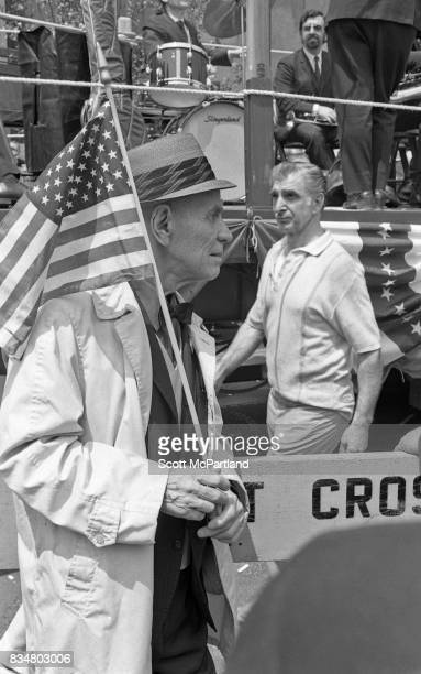 An older war veteran stands with an American Flag in hand and protests Mayor Lindsey's decision to lower the American Flags after the Kent State Ohio...