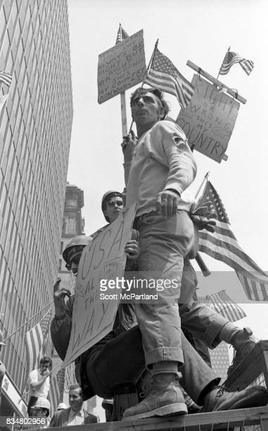 World Trade Center construction workers stand on a fence near City Hall and angrily protest Mayor Lindsey's decision to lower the American Flags in...