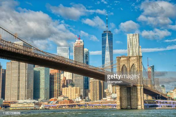 downtown manhattan with the brooklyn bridge and world trade center as seen from dumbo brooklyn new york city - new york city stock pictures, royalty-free photos & images