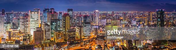 ダウンタウンの現代的な高層ビル、ネオンの夜に、大阪の街並みのパノラマに広がる輝く日本