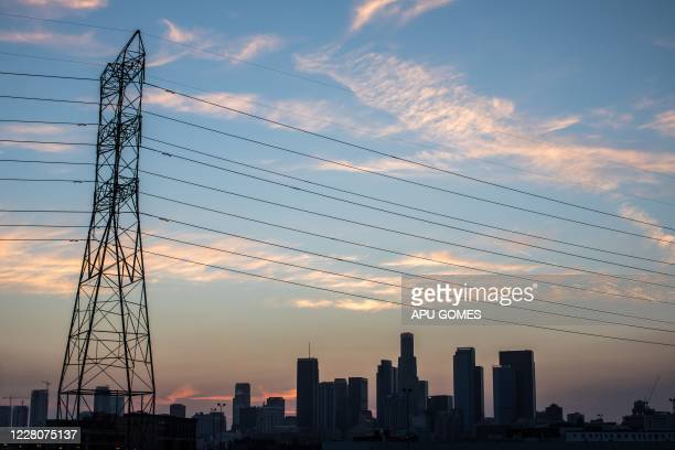 Downtown skyline is seen behind high tension towers in Los Angeles, California on August 16, 2020. - California on August 14 ordered rolling power...