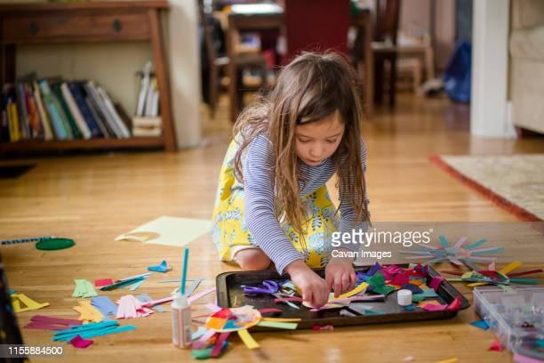 downward view of a little girl making paper art on living room floor - arte y artesanía fotografías e imágenes de stock