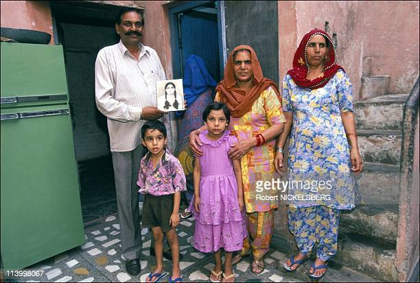 Dowry deaths In India In April, 1998-Gyan chand with pix of murdered daughter Asha.