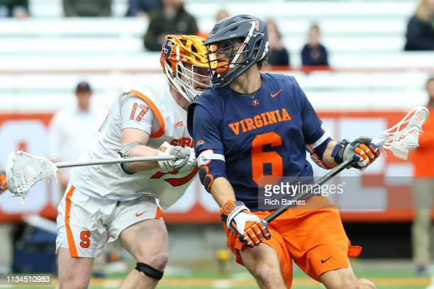 Dox Aitken of the Virginia Cavaliers dodges to the goal against the defense of Brett Kennedy of the Syracuse Orange during the first half at the...