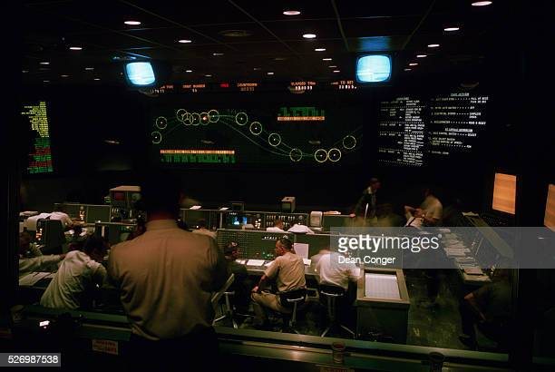 A dozen men monitor screens and radios in the mission control room of Project Mercury at Cape Canaveral Florida