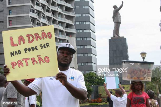 A dozen of people hold placards in down town Luanda in front of the statue of Agostinho Neto on March 17 as they protest against the amnesty provided...