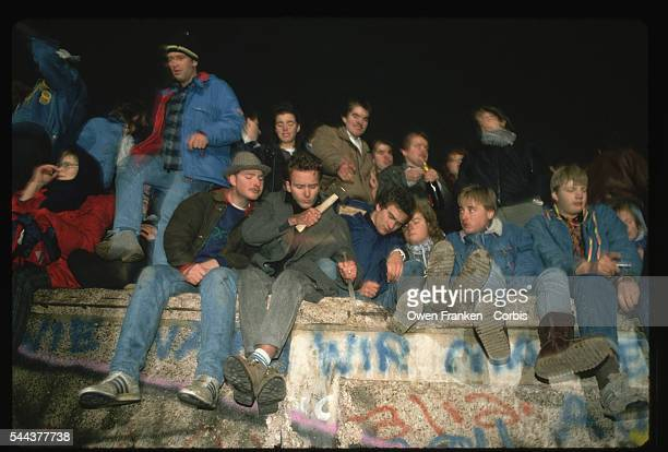 A dozen people celebrate the fall of communism in East Germany on the Berlin Wall Some are chiseling souvenir pieces