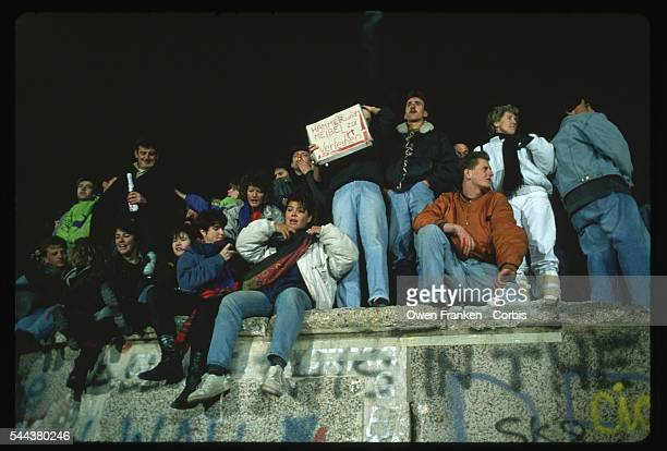 A dozen people celebrate the fall of communism in East Germany on the Berlin Wall