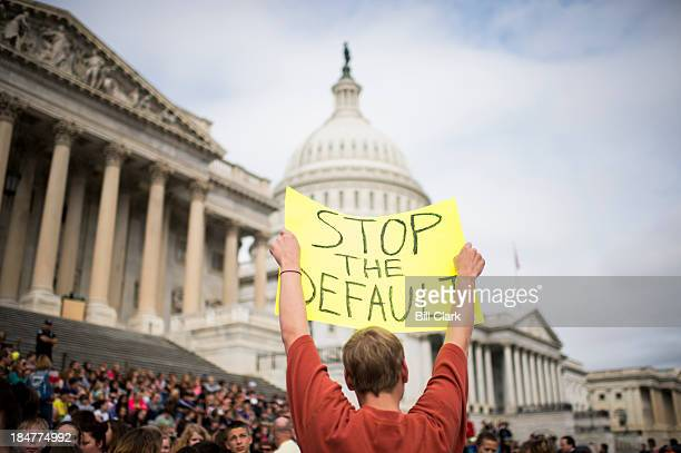 A dozen protesters mostly federal workers hold up signs at the Capitol urging Congress to end the government shutdown and avert the debt limit crisis...