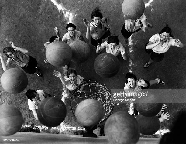 A dozen women basketball players throw balls at the hoop at once The women are students at University of California at Los Angeles participating in...
