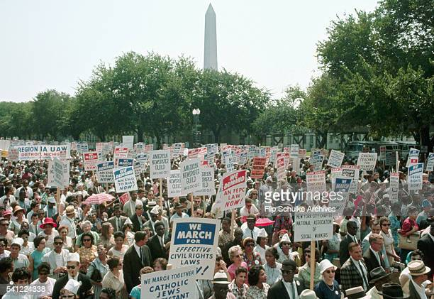 Dozens of civil rights marchers pass the Washington Monument during the March on Washington