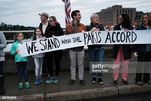 Dozens of Connecticut residents converge along a bridge at a vigil and rally for the environment and against President Donald Trump's recent decision...