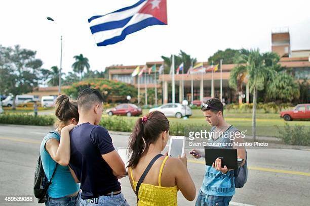 Dozens of Cubans stand in front of the Hotel Pernik and use phones tablets and laptops to get connected to the internet that has been provided for...