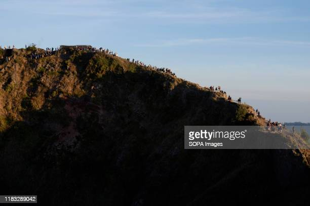 Dozens of hikers climb the east top of Mount Batur in Bali during the sunrise A popular tourist destination Mount Batur is a 1717 meter high active...
