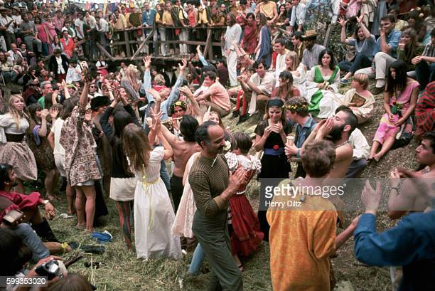 Dozens of hippies dance in a field at a renaissance fair