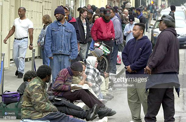 Dozens of homeless people line up for a free meal at St Anthony's church December 6 2002 in San Francisco California San Francisco has attracted...