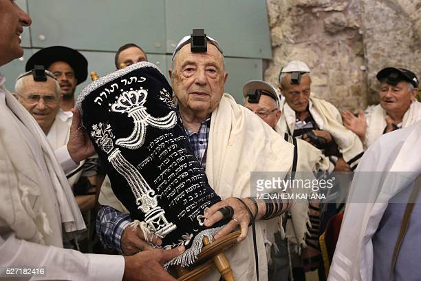 Dozens of Jewish holocaust survivors wear the Tefilin or the Phylacteries and the Tallit prayer shawl as they dance with the Torah after performing...
