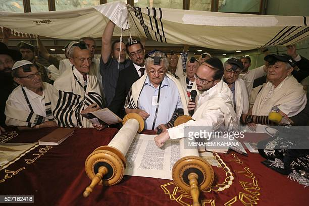 Dozens of Jewish holocaust survivors wear the Tefilin or the Phylacteries and the Tallit prayer shawl as they read from the Torah scrolls during...