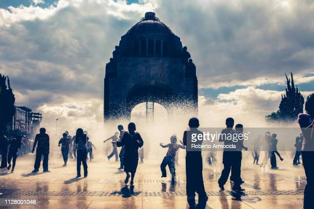 dozens of kids play in the fountains of the monument to the revolution in the center of mexico city - mexico city stock pictures, royalty-free photos & images